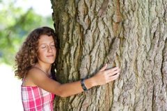 Girl With Eyes Closed Embracing Tree. Side view of teenage girl with eyes closed embracing tree Royalty Free Stock Image