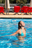 Girl with with eyes closed floating in the pool Stock Photos