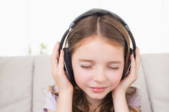 Girl with eyes closed listening music through headphones Stock Images