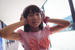 Girl with eyes closed listening music through headphones. While standing in corridor at school stock photography