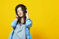 Girl with eyes closed wearing headphones. Young beautiful woman in bright outfit enjoying the music over yellow wall with copy space. Studio portrait of a girl Royalty Free Stock Images