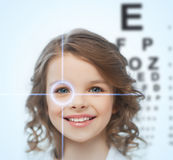 Girl with eyesight testing board. Health, vision, medicine, laser correction, happy people concept - smiling pre-teen girl with optometric table or eyesight stock image
