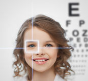 Girl with eyesight testing board. Health, vision, medicine, laser correction, happy people concept - smiling pre-teen girl with optometric table or eyesight royalty free stock images