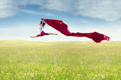 Girl with fabric dancing at field Stock Photos