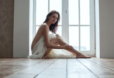 Girl with fabric siiting on floor Royalty Free Stock Photo