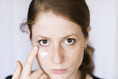 Girl with face cream. Girl putting face cream on isolated background Royalty Free Stock Photos
