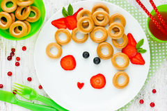 Girl face dessert or breakfast for of kids - bagels with fruit a Stock Photos