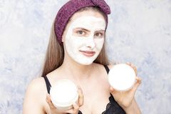 Girl with  face mask holding  jar with a face mask and a lid from a jar with a copy space stock photos