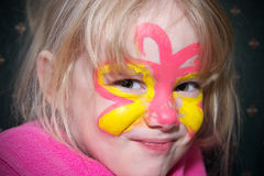 Girl with face paint. A cute little girl wearing butterfly face paint royalty free stock photo