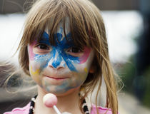 Girl with face painted. Cute little girl with butterfly face painting royalty free stock photo