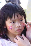 Girl face painting. Girl getting her face painte at the fair Royalty Free Stock Photography