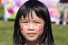 Girl face painting. Girl with her face painted at the fair royalty free stock images