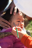Girl Face painting. Young girl getting her face painted at a festival Stock Photo