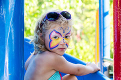 Girl with face painting. Beautiful blond girl with face painting stock photography