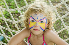 Girl with face painting. Beautiful blond girl with face painting royalty free stock images