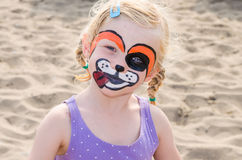 Girl with face painting. Beautiful blond girl with face painting of dog stock images