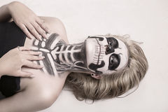 Girl on the face of skeleton. Girl on the face of the skeleton Halloween stock photography