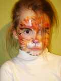 Girl with the face of the tiger. A beautiful little girl with painted face like a tiger stock image