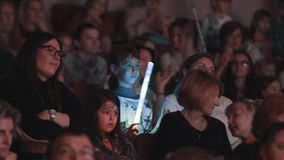 Girl with facepaint hits hand with flashing rod watching show in concert hall stock video