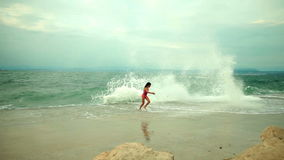 Girl faces the heavy seas and tries to avoid the spurts from the waves. Turbulent sea splashing the coastline with waves on a cloudy day with couple of kids stock footage