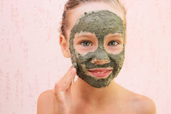 Girl with facial clay mask. Royalty Free Stock Photography