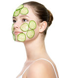 Girl with facial mask of cucumber. Portrait of young beautiful adult girl with facial mask of cucumber - isolated on white stock photo