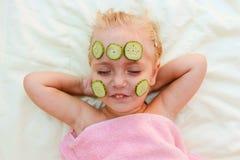 girl with facial mask of cucumber. Royalty Free Stock Photos
