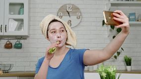Girl with facial mask makes selfie eating celery in kitchen. Girl in blue t-shirt with facial mask and towel on head makes selfie with phone eating celery in stock video footage