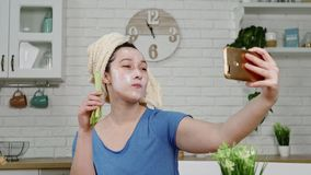 Girl with facial mask makes selfie eating celery in kitchen. Girl in blue t-shirt with facial mask and towel on head makes selfie with phone eating celery in stock footage