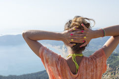 Girl facing the extraordinary view at the seaside from mountain Stock Photo