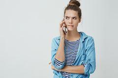 Girl facing tough troublesome choice perplexed biting lower lip frowning looking seriously aside holding smartphone royalty free stock photo
