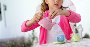 Girl in fairy costume pouring tea into cup 4k. Smiling girl in fairy costume pouring tea into cup 4k stock video