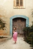 A girl in a fairy dress of a princess with a crown turns around walkng to the door of an ancient castle house. Girl in a fairy dress of a princess with a crown Stock Photos