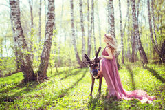 Girl in fairy dress and reindeer in the forest Royalty Free Stock Image
