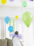 Girl In Fairy Wings With Balloons Climbing On Sofa Royalty Free Stock Photography