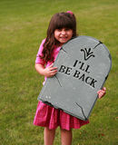 Girl with fake tombstone. Little hispanic girl outside holding a fake tombstone Royalty Free Stock Image
