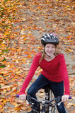 Girl on Fall Bike Path. Looking down at a happy ten-year old girl with braces sitting on her bike on a bike path in the fall Royalty Free Stock Photography