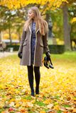 Girl on a fall day, with shoes in hand Royalty Free Stock Image