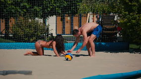 The girl fall down on sand during playing volleyball on the beach. Young couple playing volleyball on the beach near the net. The guy throw the ball to girl. The stock footage