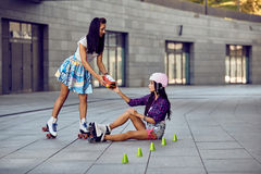 Girl fall down and scratch the leg after rollerblading. Beautiful young women offers to help protective equipment for the knees. Two girls sports fun. Active stock image
