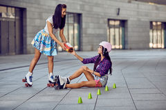 Girl fall down and scratch the leg after rollerblading. Beautiful young women offers to help protective equipment for the knees. Two girls sports fun. Active royalty free stock image