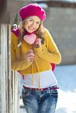 Girl in the fall dressed yellow. And violet cap with hugging hands Royalty Free Stock Photo