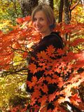 Girl in fall maple leaves. Fine outdoor seasonal vacation background representing happy smiling young woman relaxing in the fall red maple forest Stock Photo