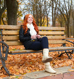 Girl in fall season listen music on audio player with headphones, sit on bench in city park, yellow trees and fallen leaves Royalty Free Stock Images