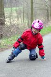 Girl fall on the skates. A girl learns to skate on roller skates Royalty Free Stock Image