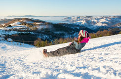 Girl falling down on the snow. Y mountain Stock Images