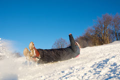 Girl falling down on the snow. Y mountain Royalty Free Stock Image