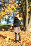 Girl in falling leaves. Excited girl - young indonesian woman with long black curly hair standing among falling maple leaves at autumn royalty free stock photo