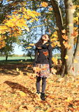 Girl in falling leaves. Excited girl - young indonesian woman with long black curly hair standing among falling maple leaves at autumn stock image