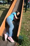 Girl falling on the slide. Little girl falling on the slide at the park on sunny day Royalty Free Stock Photo